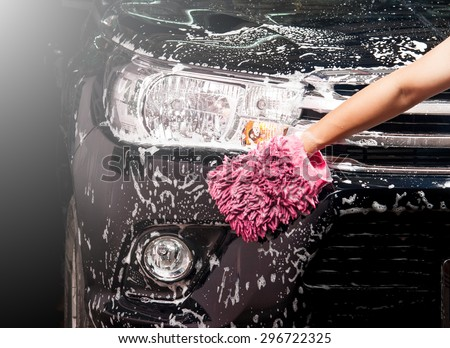 man washing a soapy black car with a cloth - stock photo