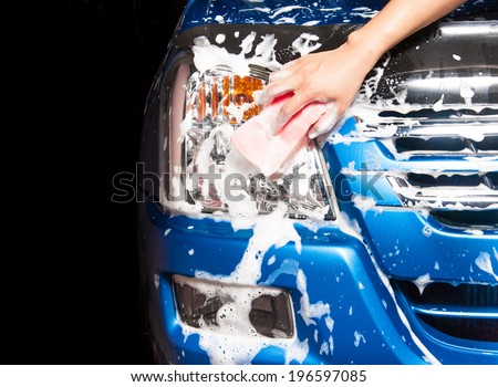 man washing a soapy blue car with a pink sponge