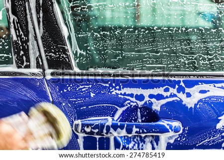 man washing a soapy blue car with a yellow sponge. - stock photo