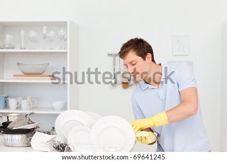 Man washing dishes  in the kitchen - stock photo