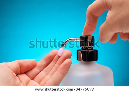 Man washing his hands with liquid soap. Blue background. - stock photo