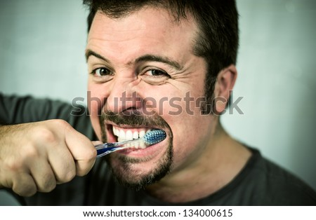 Man washing his teeth in front of the mirror - stock photo