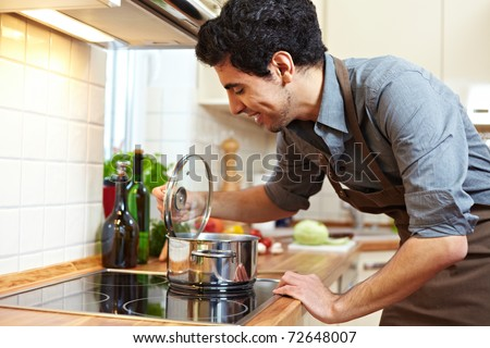 Man watching a pot on a stove in the kitchen
