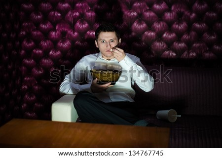 Man watching fascinating program in TV and eating popcorn - stock photo