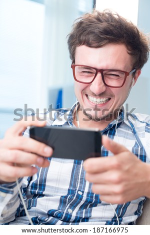 Man watching funny video on his phone with earphones - stock photo