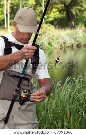 man watching his fishing rod in front of a river - stock photo