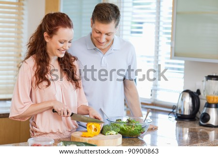 Man watching his girlfriend preparing a salad in the kitchen - stock photo