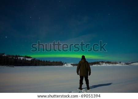 Man watching Northern Lights (Aurora borealis) over moon lit snowscape of frozen lake and forested hills. - stock photo