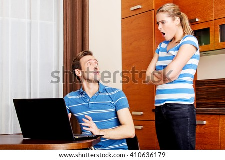 Man watching something on laptop, his wife is angry - stock photo