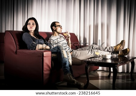 Man watching sports and woman bored. Conflict about the tv program. - stock photo