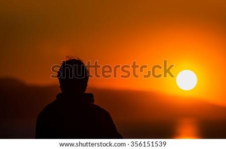 man watching sunset at beach - stock photo