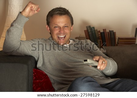 Man Watching Television Excitedly - stock photo