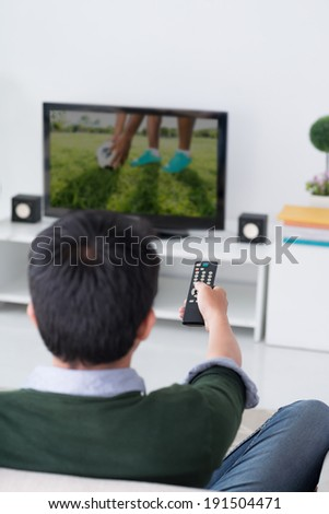 Man watching television in the living room, rear view