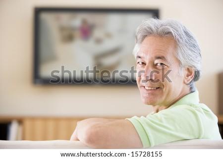Man watching television smiling - stock photo