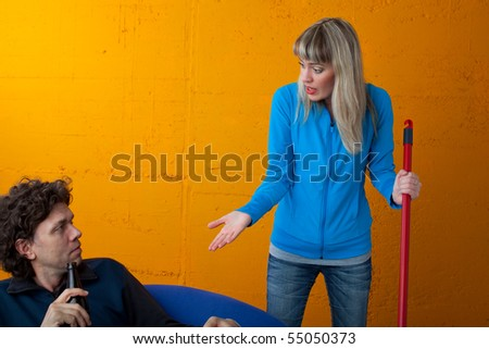 man watching telly while the wife is cleaning - stock photo