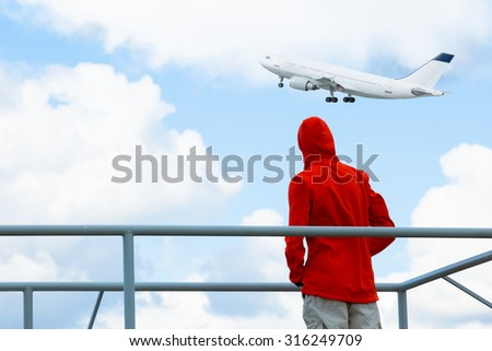 MAN WATCHING THE FLYING PLANE - stock photo
