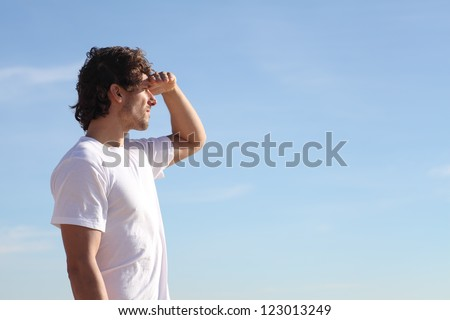 Man watching the sky with his hand in the forehead - stock photo