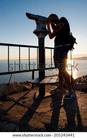 Man watching through panoramic telescope in Lubenice - Croatia - stock photo