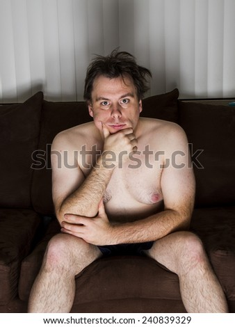 Man watching TV or thinking while sitting on the couch. - stock photo