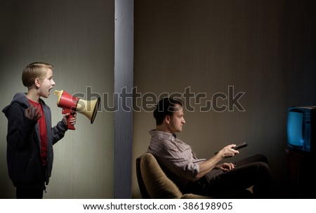 Man watching TV while his son calling him through a megaphone. Lack of father's attention concept