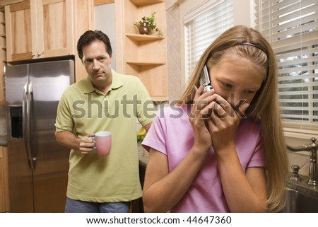 Man watching young girl talk secretively on cell phone.  Vertically framed shot. - stock photo