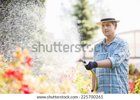 Man watering plants outside greenhouse - stock photo
