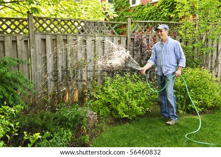 Man watering the garden with hose in backyard - stock photo