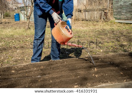 man watering the planted seeds , flower bed , flower bed at the cottage