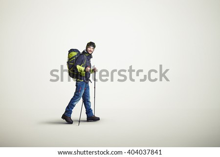 Man wear winter clothes with hiking poles and bag, on white background - stock photo