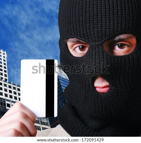 man wearing a balaclava and holding a credit card - stock photo