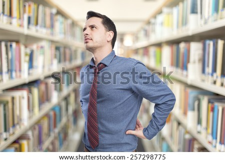 Man wearing a blue shirt and red tie. He doing a backache gesture. Over library background