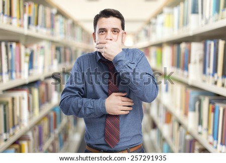 Man wearing a blue shirt and red tie. He is covering his mouth with his hands. Over library background - stock photo