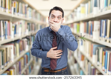 Man wearing a blue shirt and red tie. He is looking scared. Over library background - stock photo