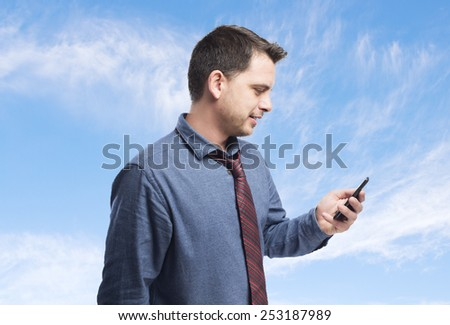 Man wearing a blue shirt and red tie. He is using a smartphone. Over clouds background - stock photo