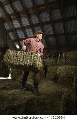Man wearing a cowboy hat and carrying bales of hay in the barn. Vertical shot.