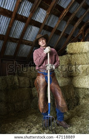Man wearing a cowboy hat and chaps leaning on a pitchfork. Behind him are bales of hay. Vertical shot. - stock photo