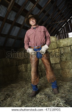 Man wearing a cowboy hat and chaps standing confidently in a barn with bales of hay in the background. Vertical shot.