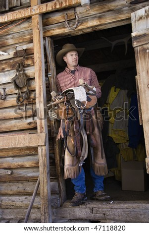 Man wearing a cowboy hat, leaning in the doorway of log cabin and holding a saddle. Vertical shot. - stock photo