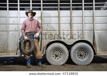 Man wearing a cowboy hat, leaning on the side of a livestock trailer. He is holding a lariat. Horizontal shot. - stock photo