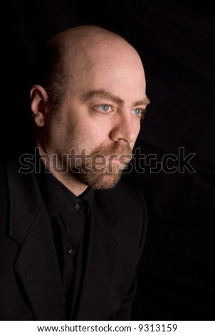 Man wearing a dark shirt and jacket over a black background - stock photo