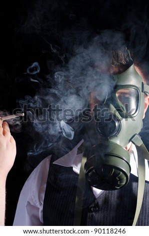 Man wearing a gas mask for protection against cigarette smoke - stock photo