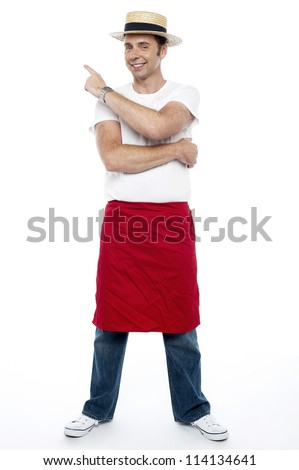 Man wearing a hat and apron pointing away at the copy space area - stock photo