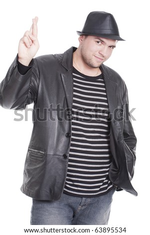 man wearing a hat and crossing fingers - stock photo