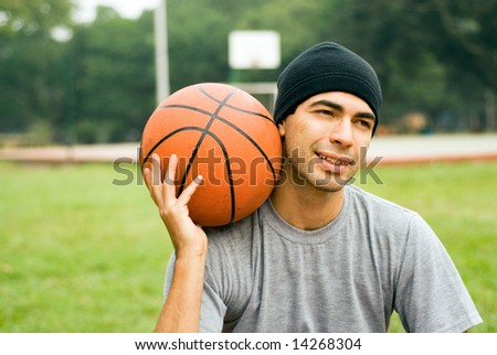 Man wearing a hat is sitting down in a park holding a basketball.  There is a basketball court behind him.  He appears to be amused.  Horizontally framed shot. - stock photo