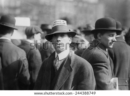Man wearing a Industrial Workers of the World Hat Card reading 'Bread or Revolution' in a rally at New York City's Union Square. Ca. 1914.