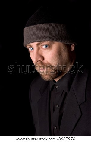 Man wearing a knit hat over a black background - stock photo