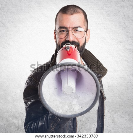 Man wearing a leather jacket shouting by megaphone