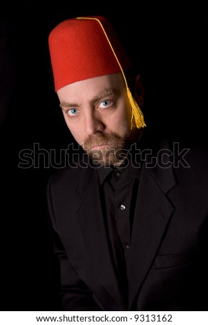 Man wearing a red shriners fez over a black background - stock photo