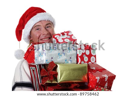 man wearing a santa hat with an armful of Christmas Gifts - stock photo