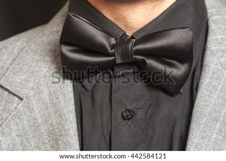 Man wearing a  suit and bow tie on black background - stock photo